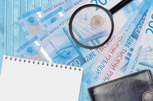 Банкноты 2000 российских рублей и увеличительное стекло с черным кошельком и блокнотом. понятие о поддельных деньгах. поиск различий в деталях денежных купюр для обнаружения фальшивых денег Premium Фотографии