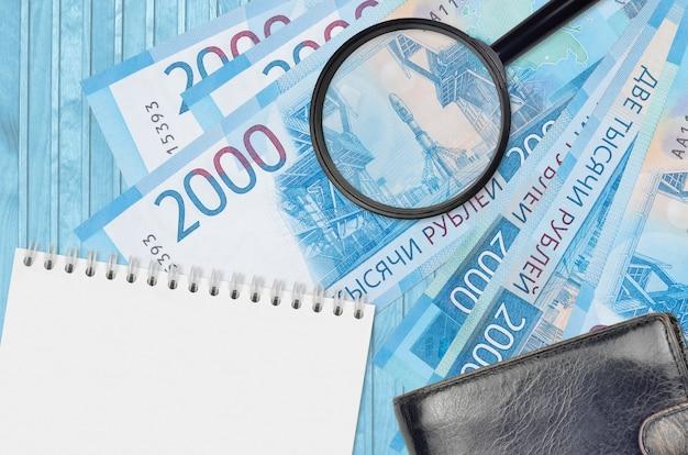 Банкноты 2000 российских рублей и увеличительное стекло с черным кошельком Premium Фотографии