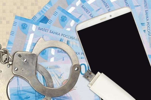 Купюры 2000 российских рублей и смартфон с полицейскими наручниками Premium Фотографии
