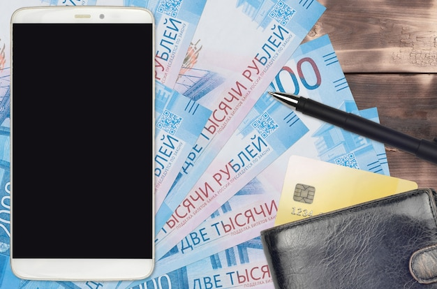 Банкноты 2000 российских рублей и смартфон с кошельком и кредитной картой. электронные платежи или концепция электронной коммерции. интернет-магазины и бизнес с использованием портативных устройств Premium Фотографии