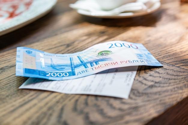Новые российские банкноты номиналом в 2000 рублей в мужской руке он собирается оплатить счет в ресторане Premium Фотографии