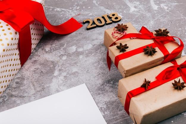 クリスマスツリーは、赤い現在のボックスと番号2018で作られた空白のカードの上に灰色の床に横たわっている 無料写真