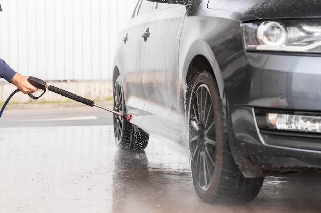 男はセルフサービスの洗車で車を洗っています。高圧車両洗浄機は泡を吹き付けます。ムラダボレスラフ、2019年12月12日 Premium写真