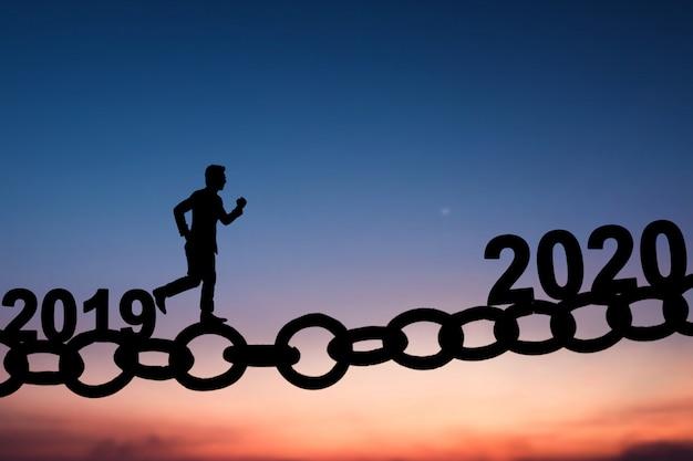 Силуэт делового человека, идущего и бегущего по цепному мосту с 2019 по 2020 год Premium Фотографии