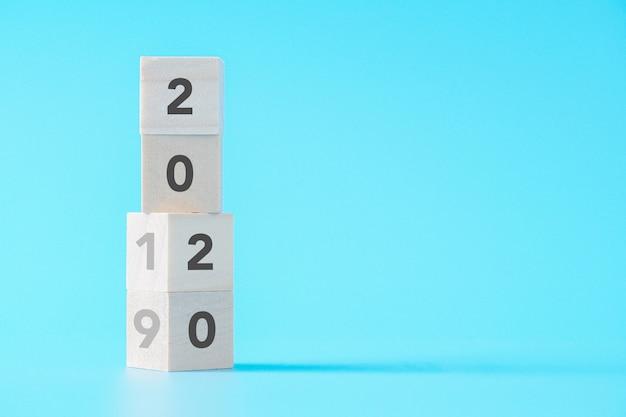 Деревянные кубики меняется с нового года 2019 до 2020 года концепции на изолированном фоне с копией пространства Premium Фотографии