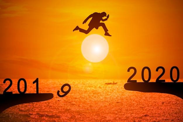 Силуэт молодой бизнесмен прыгает с 2019 по 2020 год Premium Фотографии