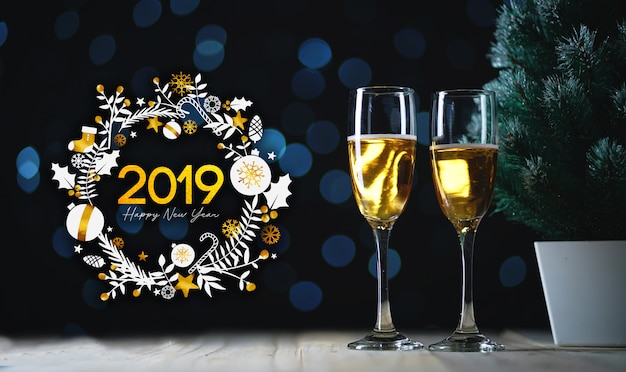 2019タイポグラフィアート。シャンパンと小さなクリスマスツリーの2つのメガネダークグローライトの背景 Premium写真