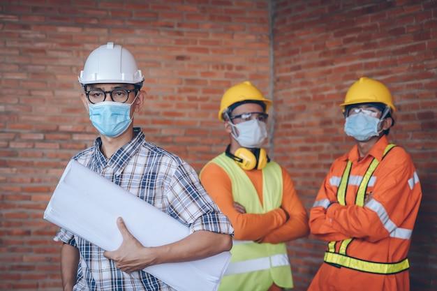 Инженер носить защитные маски для лица безопасности для коронавирусной болезни 2019 (covid-19) на строительной площадке, концепции здравоохранения и строительства. Premium Фотографии