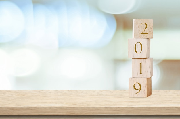 2019 happy new year greeting card, wooden cubes with 2019 over blur bokeh background Premium Photo