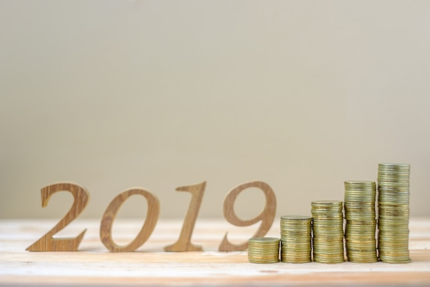 2019 happy new year with gold coins stack and wooden number Premium Photo