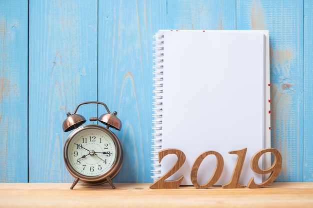 2019 happy new years with notebook, retro alarm clock and wooden number Premium Photo
