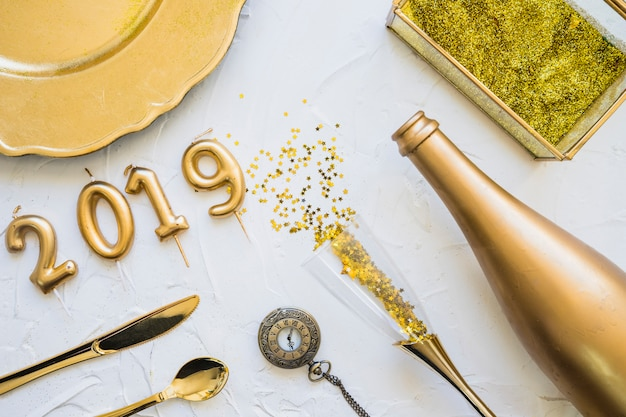 2019 inscription from candles with bottle on table Free Photo