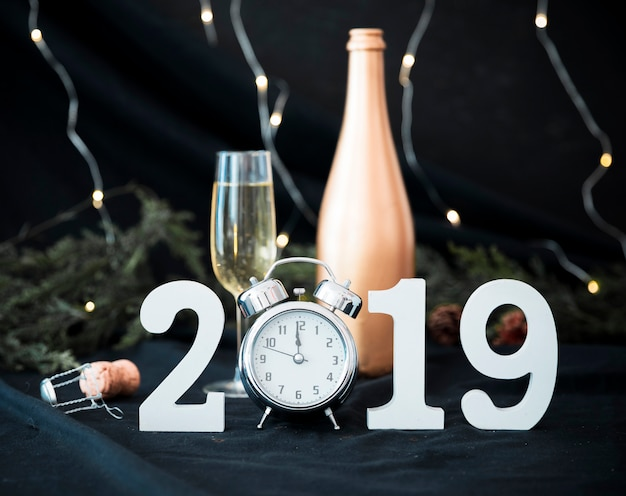 2019 inscription with clock and glass on table Free Photo