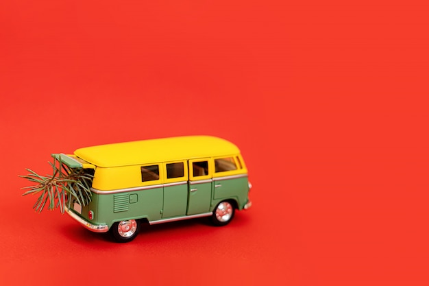 2019 miniature hippy car with fir tree on red background Premium Photo
