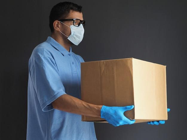 医療用マスクと手袋をした男が小包を配達しました。段ボール箱の宅配便。流行中のパンデミックコロナウイルス2019-ncov、covid-19ウイルス中の宅配サービス。 Premium写真