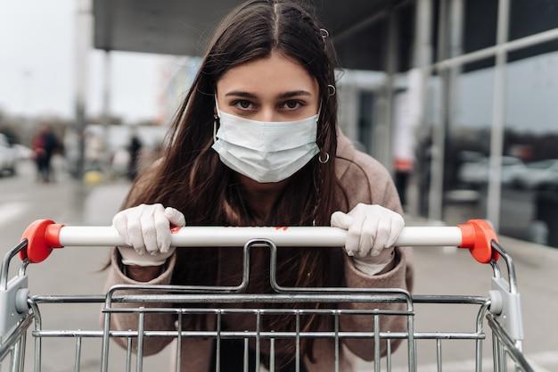 ショッピングカートを押すコロナウイルス2019-ncovに対する保護フェイスマスクを着た若い女性。 無料写真