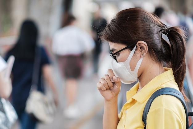 公共の駅で新規コロナウイルス(2019-ncov)または武漢コロナウイルスに対する保護マスクを身に着けている若いアジア女性は、呼吸器感染症を引き起こす伝染性ウイルスです。 Premium写真