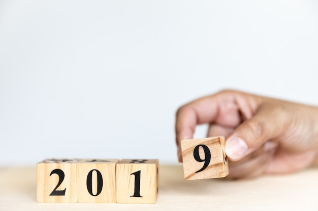 2019 new year concept design with hand is putting wooden cube of number nine Premium Photo
