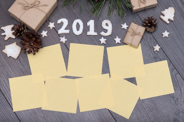 2019 numbers from cookies  with gifts, fir, pine on wooden background. new year. wishes an Premium Photo