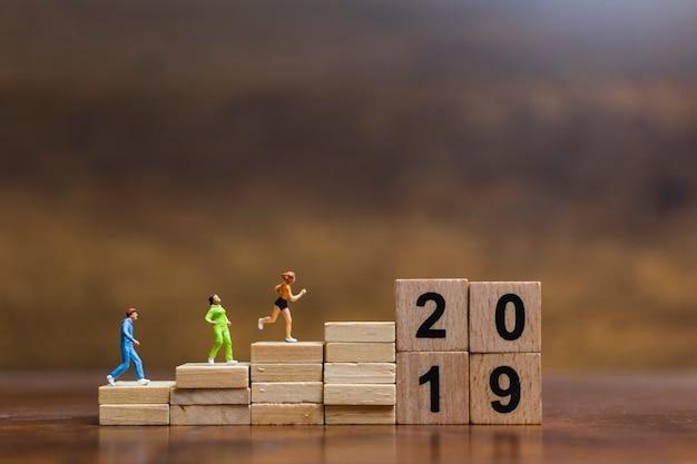 木製ブロック番号2019で走っているミニチュア人 Premium写真