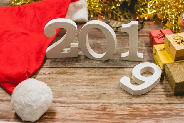 木製の背景にクリスマスの帽子、2019番号とギフトボックスのトップビュー。 Premium写真