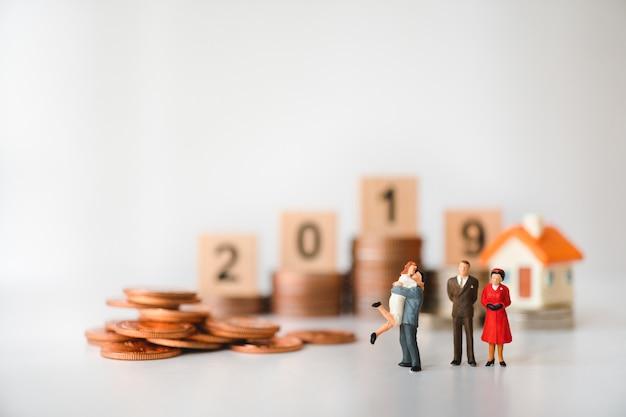 ミニチュア人、スタックコインと2019年の背景を持つ家族 Premium写真