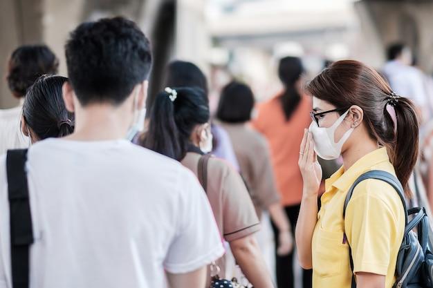 Молодая азиатская женщина, носящая защитную маску против нового коронавируса (2019-нко) или коронавируса ухань на общественном вокзале, является заразным вирусом, вызывающим респираторную инфекцию. концепция здравоохранения Premium Фотографии