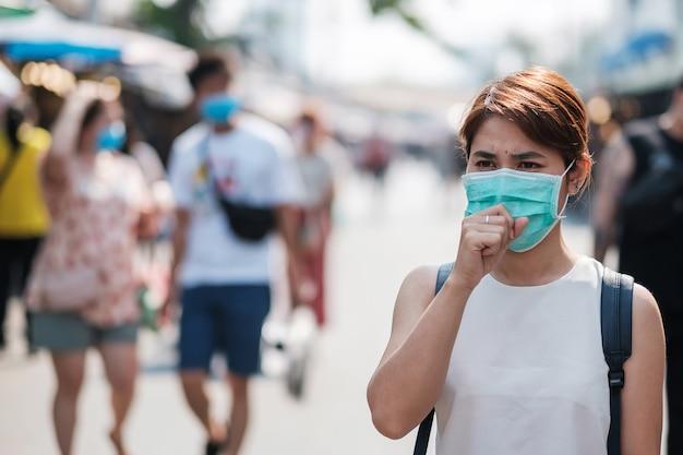 Молодая азиатская женщина в защитной маске от нового коронавируса (2019-нков) или коронавируса ухань на рынке выходного дня чатучак, достопримечательность и популярность среди туристов Premium Фотографии