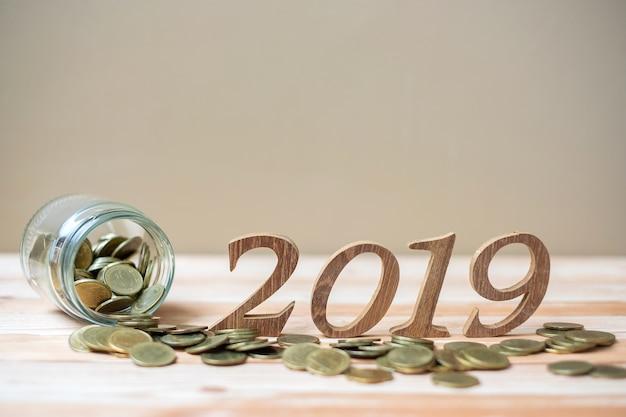 2019年金のスタックとテーブル上の木製の数字と新年あけましておめでとうございます Premium写真
