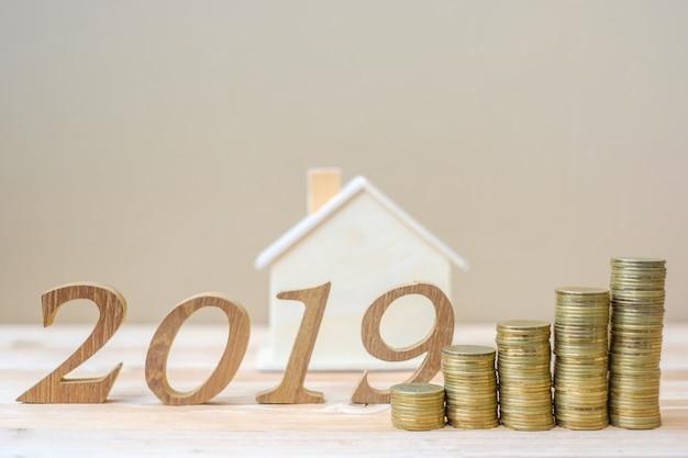 2019年金の金貨のスタックと木製の数字でハッピーニューイヤー Premium写真