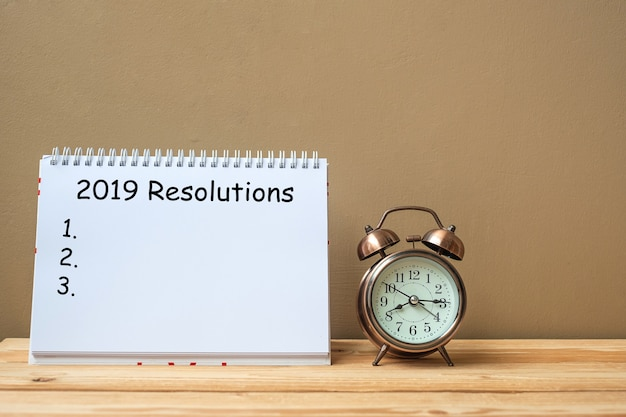 2019テーブル上のノートブックとレトロ目覚まし時計の解像度テキスト Premium写真