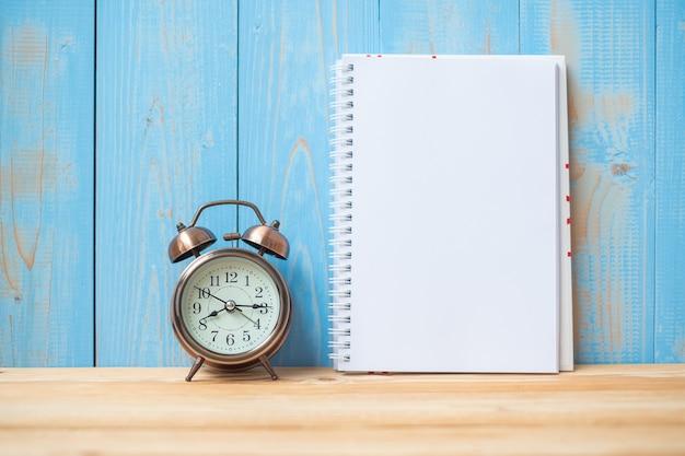 ノートブック、レトロな目覚まし時計がテーブルに2019年の新しい年 Premium写真