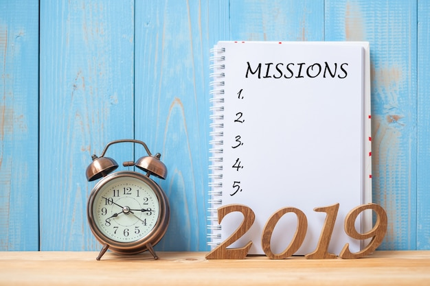 ノートブック、レトロ目覚まし時計にミッションのテキストが付いている2019年の幸せな新しい年 Premium写真