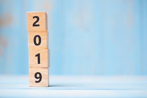 テキストのコピースペースを持つ青いテーブル背景に2019年新年木製キューブ Premium写真