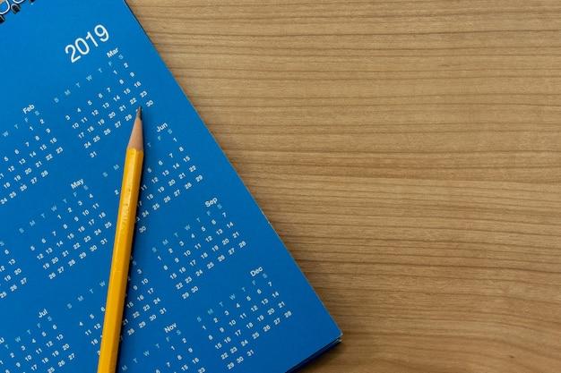 予定を作成するために青い2019カレンダー月スケジュールに黄色の鉛筆 Premium写真