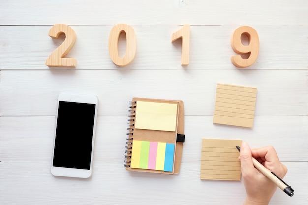 2019木製の手紙、白紙のメモ用紙、ウッドの背景にスマートフォン上にペンを持つ手 Premium写真