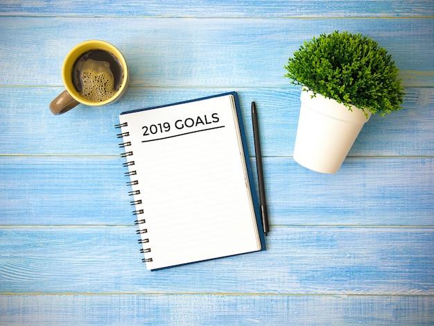 ノートパソコンの手書きの目標のトップビュー2019年青い木製のテーブルに。 Premium写真