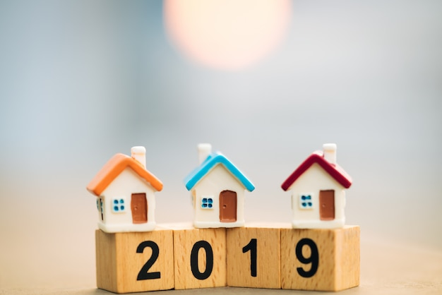 木製ブロックワード2019新年とコインスタックの上に家。 Premium写真