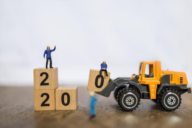 2020 новый год, работа и бизнес-концепция. закрыть группу рабочих миниатюрных людей, работающих с игрушечным погрузчиком машина машина загружен номер 0 деревянный блок, чтобы сложить блок на деревянный стол и скопировать пространство Premium Фотографии