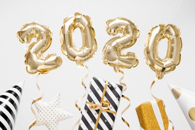 新年あけましておめでとうございます2020のお祝い。ギフトと白い背景の上の金箔風船数字2020 Premium写真