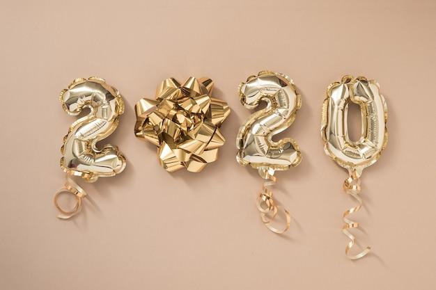 Празднование нового года 2020. золотая фольга шары цифра 2020, изолированные на пастельных бежевом фоне Premium Фотографии