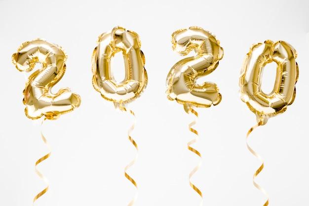 新年あけましておめでとうございます2020のお祝い。白い背景の空気にぶら下がっている金箔風船数字2020 Premium写真