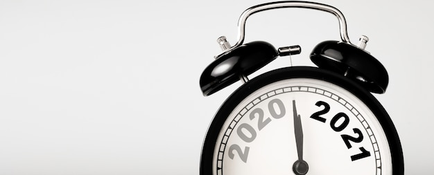 2020 and 2021 on black alarm clock with copy space, merry christmas and happy new year concept. Premium Photo