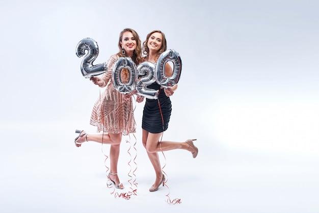 白の金属2020風船を持つ2つの幸せなガールフレンド。 Premium写真