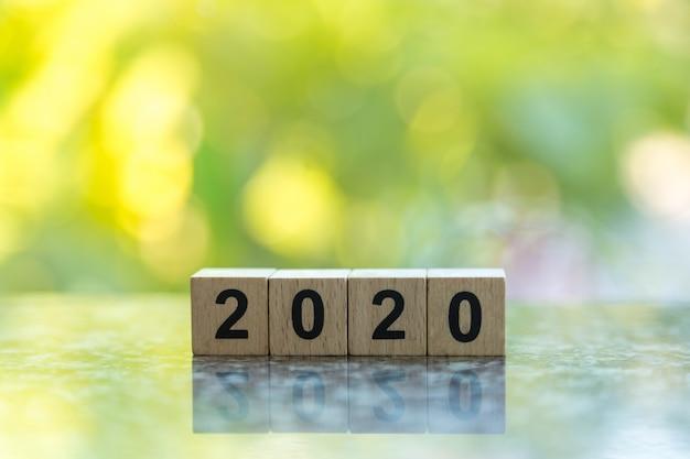 Закройте вверх деревянной игрушки блока номера 2020 на земле с природой лист зеленого цвета bokeh Premium Фотографии