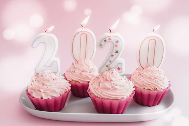 2020 candles on cupcakes with whip cream frosting using pink silicone reusable cups Premium Photo