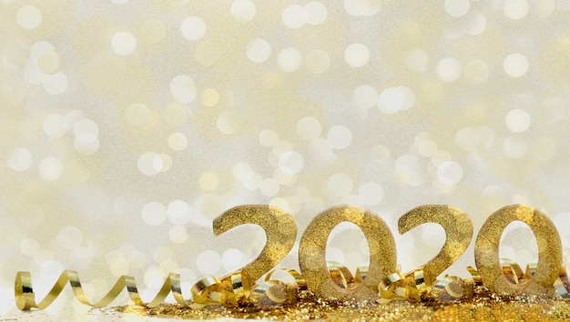 2020 golden figures in glitter and ribbon on abstract blur light background Premium Photo