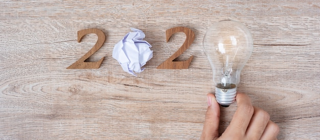 2020 happy new year with businessman holding lightbulb with crumbled paper Premium Photo