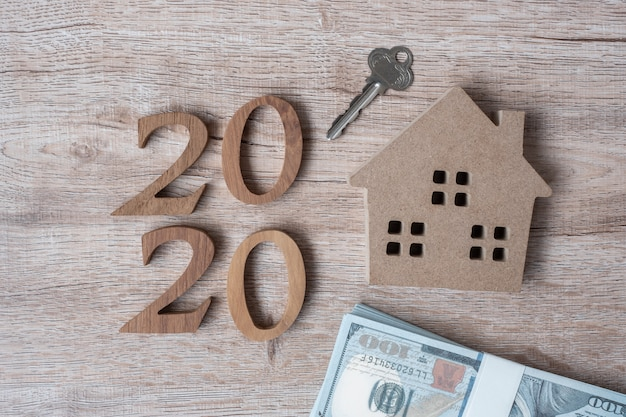 2020 happy new year with house model and money on wooden background. Premium Photo