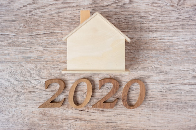 2020 happy new year with house model on wood table Premium Photo